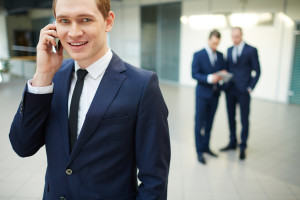 Young businessman calling and looking at camera in working envir
