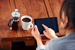 Young woman uses tablet while relaxing at home with coffee on th