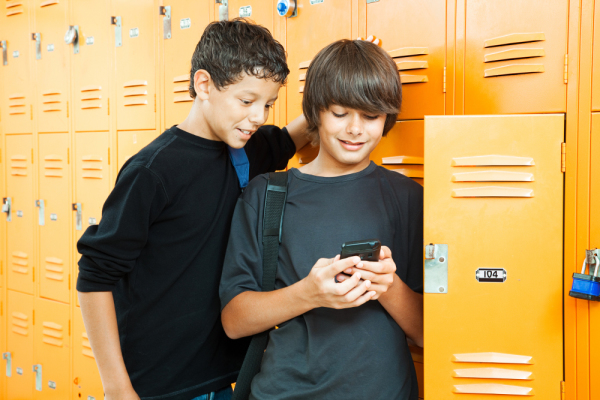 Two teenage boys playing a handheld video game in school by thei