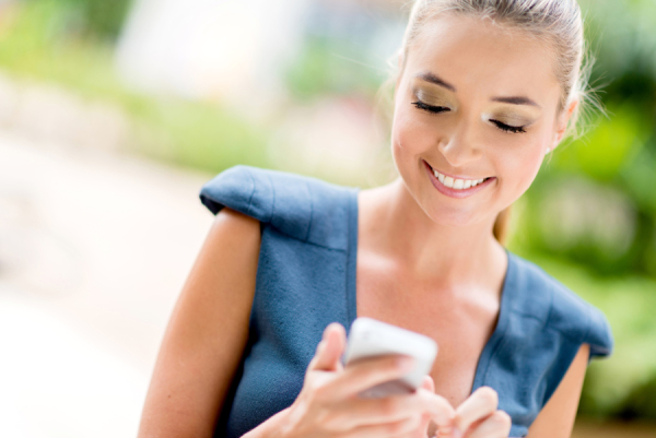 Portrait of a happy business woman texting on her phone